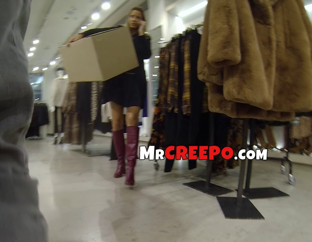 Gorgeous woman carrying a big box in store